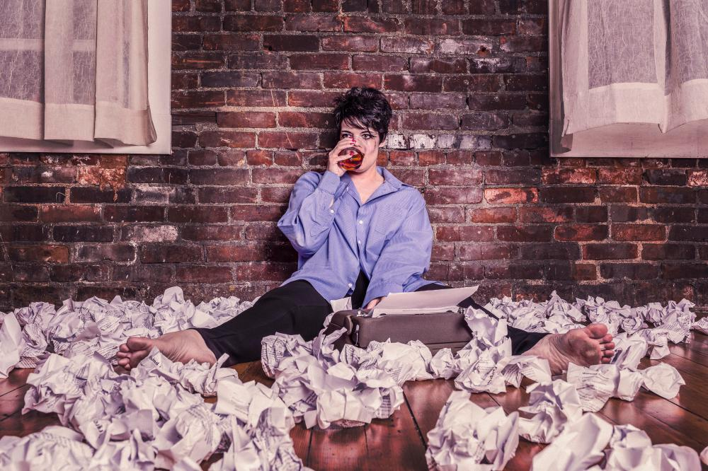 woman sits among lots of paper